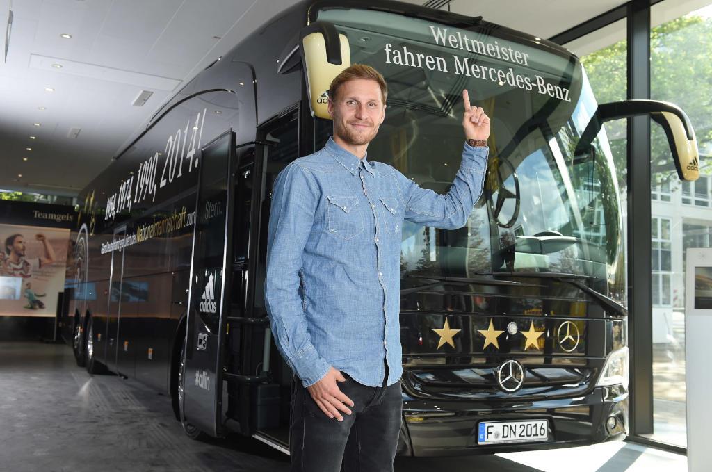 Benedikt Höwedes und der Weltmeister Bus (Bild: Daimler AG)